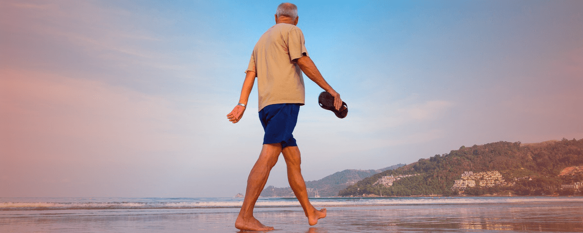 Gesunde Herzklappen ermöglichen einem älteren Herren den Strandspaziergang.