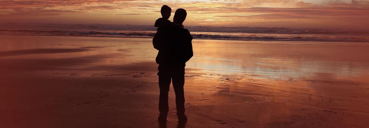 Ein älterer Mann mit seinem Enkel auf dem Arm am Meer - nach der TAVI zurück im Leben.