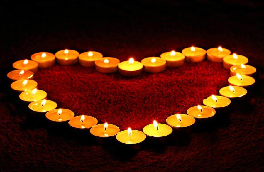 Symbolbild vom Herz beim Menschen - ein Herz aus brennenden Kerzen.
