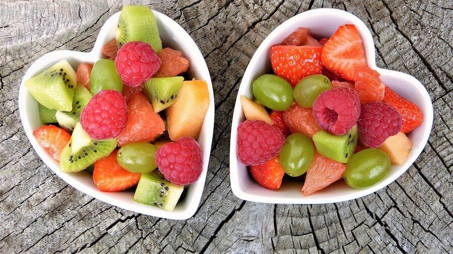 Obst in herzförmigen Schalen - mit Gesunder Ernährung lässt sich Aortenklappenersatz vorbeugen.