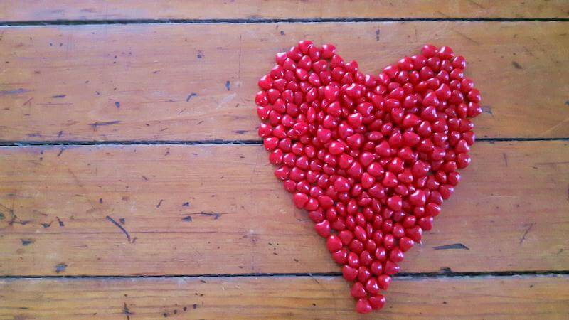 Ein großes Herz auf einem Tisch, gelegt aus kleinen roten Herzen - auch nach dem TAVI-Eingriff und der Reha lohnt sich ein gesunder Lebensstil.
