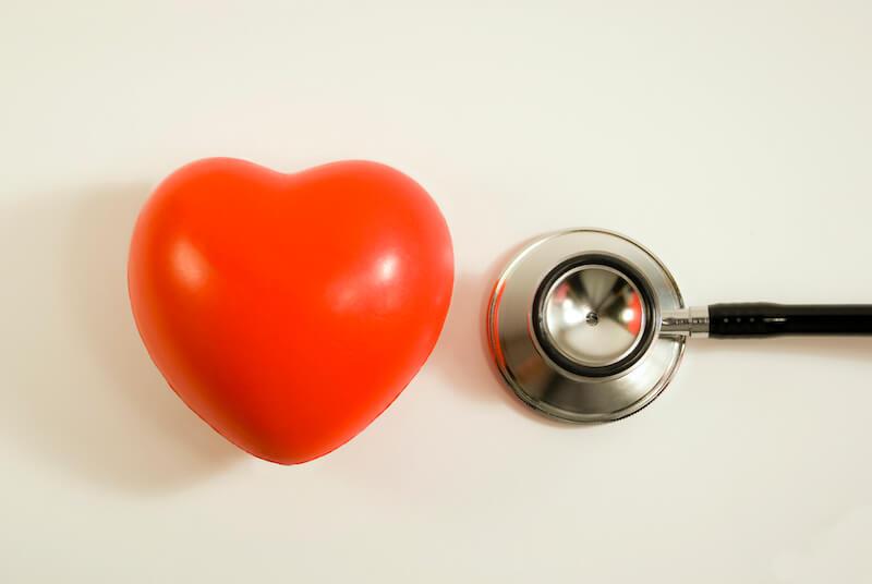 Symbolbild für Herzklappen - ein Herz aus Stein neben einem Stethoskop.
