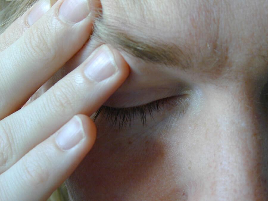 Aufgrund einer Aortenklappenstenose ist einer Frau Schwindelig. Sie fasst sich an den Kopf.